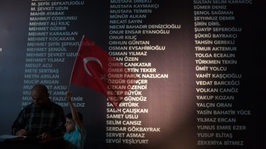 A young boy holds a Turkish flag in front of a board, at Taksim Square, listing the names of people killed during last week's failed coup attempt. The death toll now stands at 246 and 1536 wounded.