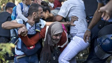 A woman is trampled as migrants and refugees push through police lines in Tovarnik, Croatia, on Thursday.