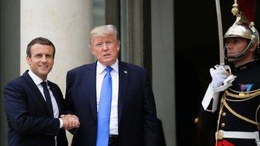 French President Emmanuel Macron, left, welcomes US President Donald Trump.