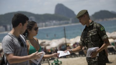 An army soldier distributes a pamphlet about the Aedes aegypti mosquito that spreads the Zika virus on the edge of the Copacabana beach in Rio de Janeiro on Saturday.