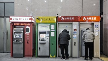People use automated teller machines in Beijing, China.