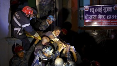 Rishi Khanal is taken out of a collapsed building by police and the French rescue team.