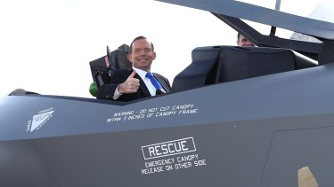 Former prime minister Tony Abbott poses in the cockpit of a replica of the F-35A Lightning II Joint Strike Fighter at Canberra's Fairbairn Airbase in April 2014.