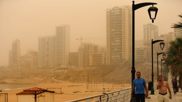 Lebanese walk on the Ramlet al-Baida seaside as a sandstorm shrouds the coastal capital of Beirut.