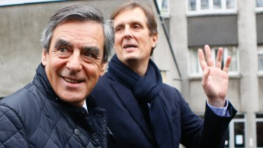 Fillon, left, leaves his campaign headquarters after delivering a speech in Paris.