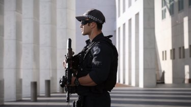 An armed AFP officer stands guard outside Parliament House in Canberra.