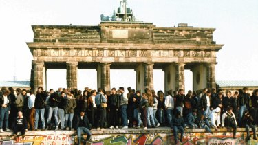 Germans from East and West stand on the Berlin Wall, one day after the wall opened in 1989.
