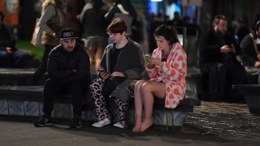 People evacuated from buildings in Wellington check their mobile phones.