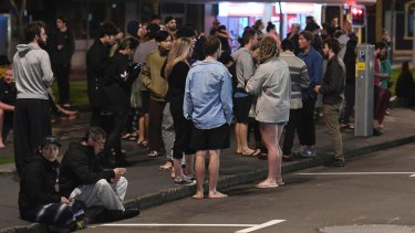 People evacuated from buildings stand in the street in the capital, Wellington.
