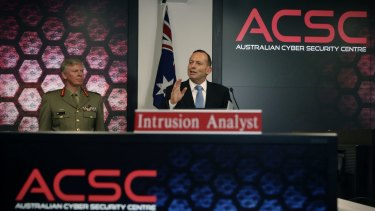 Mr Abbott, pictured with General Stephen Day, announces a cyber security review.