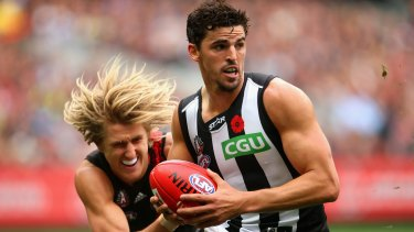 Magpies captain Scott Pendlebury is tackled by Dyson Heppell.