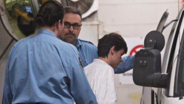 Alexandre Bissonnette is escorted to a van after appearing in court for Sunday's deadly shooting.