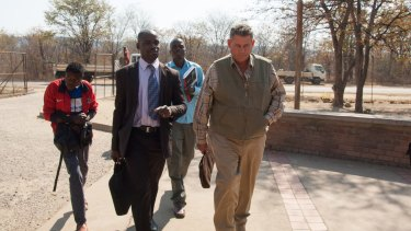 Theo Bronkhorst, right, a professional hunter, arrives for his appearance at the magistrates courts in Hwange, Zimbabwe, in July 2015.