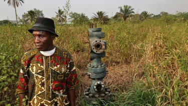 A Nigerian tribal chief stands alongside an abandoned oil wellhead, known as number 1 and previously operated by Royal Dutch Shell, in marshland in southern Nigeria.