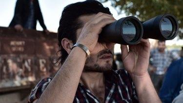 A Kurdish man watches fighting in Kobane.