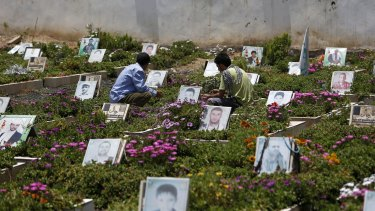Shiite rebels, known as Houthis, pray at portrait adorned graves of Houthi fighters in Sanaa last week.