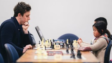 Labor MLA Michael Pettersson takes on Garran primary school student Hannah Ni in the ANU Open Chess Tournament on Sunday.