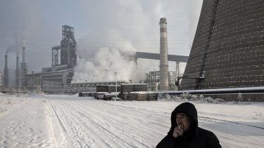 A man smokes a cigarette near a Tonghua Iron & Steel's plant in Jilin province. Pressure on media comes as the Communist Party faces rising criticism over its handling of the slowing economy.