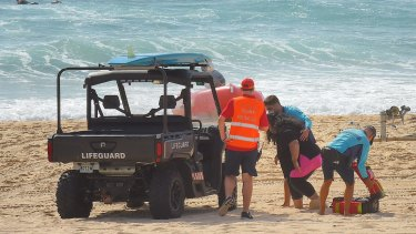 Mother Sandra Tomano is helped by lifesavers' buggy on Tuesday.