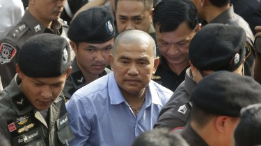 """Thai police escort the fortune teller Suriyan, better known by the nickname """"Mor Yong"""", as he arrives at military court in Bangkok on Wednesday."""