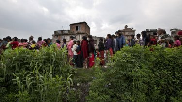 Villagers stand in a queue to receive food.