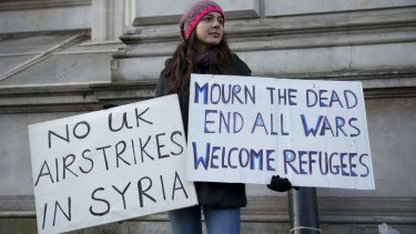 A peace protester holds placards outside Downing Street, London, on Tuesday.