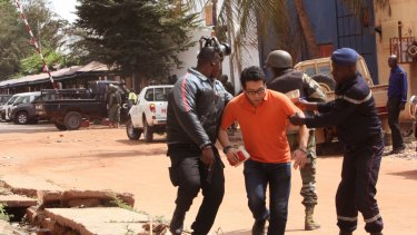 Mali security forces assist a hostage during Friday's attack.