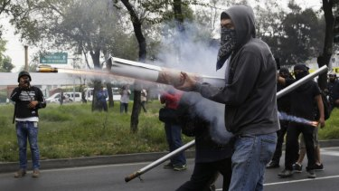 Makeshift weapons: Demonstrators fire fireworks towards riot police during a protest over the missing Ayotzinapa students, near the Benito Juarez International airport in Mexico City.