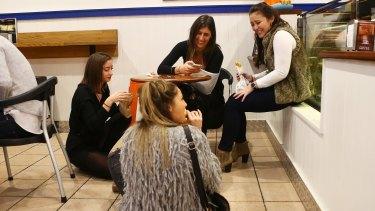Women enjoy a meal in the floor of a pie restaurant in Newtown.
