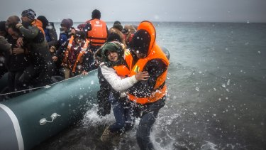 Refugees and migrants disembark on a beach in Greece at the start of the year. By the end of 2016, 65 million people had been uprooted by violence or natural disasters.