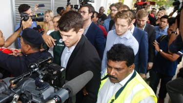 James Paver, centre left, Nick Kelly, centre with glasses, and Thomas Whitworth, centre right, of the nine Australian men arrested are escorted to the Sepang Magistrate in Sepang on Thursday.