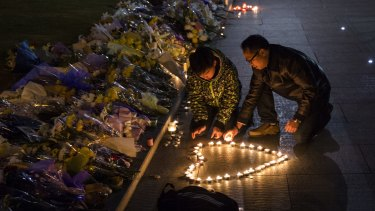 Mourners light candles at a makeshift memorial at the site of a stampede in Shanghai that left at least 36 people dead.