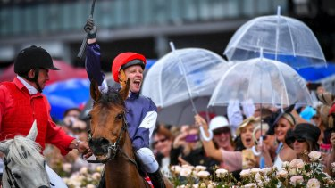 Jockey Kerrin McEvoy celebrates after winning the Melbourne Cup, as racegoers brought out their umbrellas.