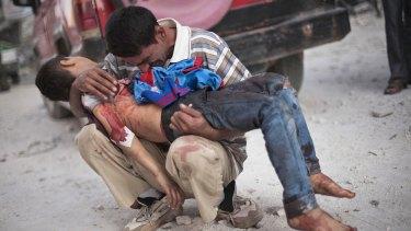 A man holds the lifeless body of his son near Dar al-Shifa hospital in Aleppo in October 2013.