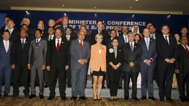 Heads of delegations pose for a photograph during the opening of the Bali Process regional ministerial meeting.