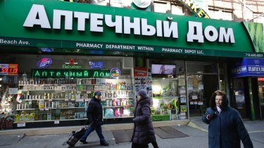 People walk past a pharmacy that caters to the Russian community in Brooklyn, New York. Russian-speaking expatriates in the city have shrugged off accusations that Kremlin hacking helped sway the presidential election.