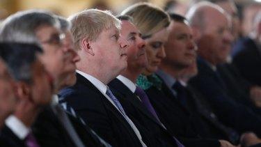 Britain's Foreign Secretary Boris Johnson, centre, listens to the speech.