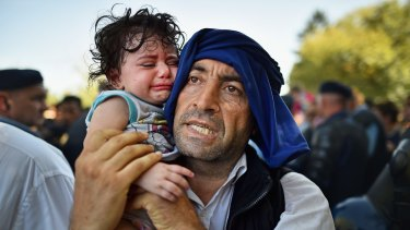A man holds his crying child close to him as migrants force their way through police lines at Tovarnik station for a train to take them to Zagreb, Croatia on Thursday.