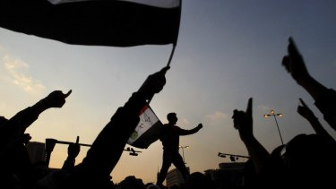 Egyptian protesters wave national flags as they chant slogans against the ruling military council at Tahrir Square, the focal point of Egyptian uprising in Cairo, Egypt, in November 2011.