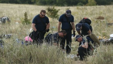 Australian Federal Police officers and their Dutch coutnerparts collect human remains from the MH17 crash site in the fields outside the village of Grabovka in the self-proclaimed Donetsk Republic, Ukraine on August 2, 2014.