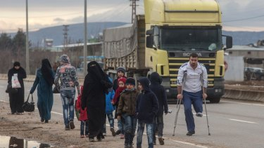A truck arriving at the border passes people walking towards a temporary housing complex at the closed Turkish border gate in Kilis on Sunday.