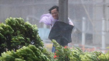 A man holds onto a lamp post against strong wind as Typhoon Hato hits Hong Kong on Wednesday.