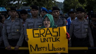 A protester holds a banner during a demonstration against the death penalty of death row prisoner Merry Utami at Wijayapura port, the entrance gate to Nusakambangan prison, on Thursday.