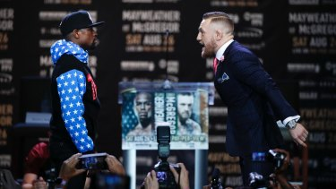 Turn up: Conor McGregor taunts Floyd Mayweather jnr at a press conference for their August bout.