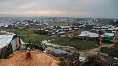 A Rohingya Muslim child, who crossed over from Myanmar into Bangladesh, plays in front of her makeshift tent .
