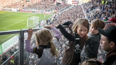 Children watch the game from the kindergarten balcony in the FC St. Pauli soccer team's stadium in Hamburg, Germany.