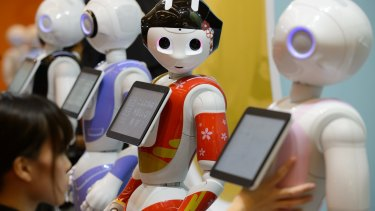 Humanoid robots stand in a row ahead of an exhibition held by SoftBank in Tokyo last year.