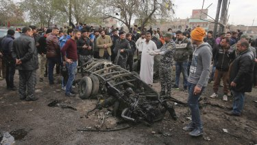 Security forces inspect the scene after a car bomb killed dozens at a crowded outdoor market in Baghdad on Monday.