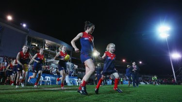 Daisy Pearce of the Demons leads the team out during this year's AFL women's exhibition match at Whitten Oval.