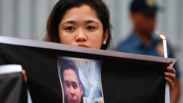 A protester displays a portrait of slain Kian Loyd delos Santos, a 17-year-old grade 11 student, who was killed by Philippine police last.